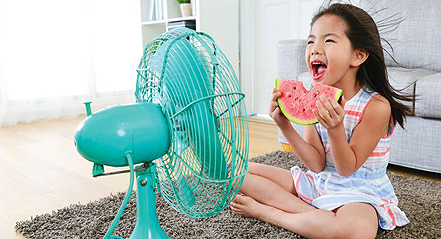 Child eating watermelon by a fan representing the clean air services of residential HVAC company Steve Chapman's All American Air in St. Augustine, FL