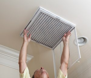 An HVAC professional changing an air filter