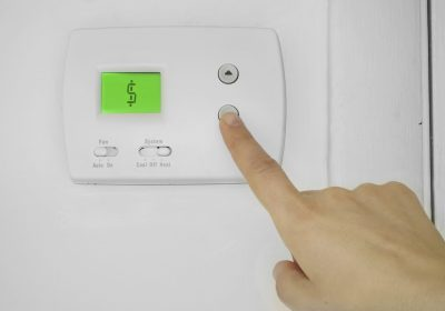 A person pressing a button on a thermostat