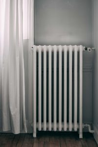 Old heater in a room next to a white curtain